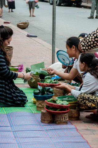 Purchasing breakfast alms to give, Luang Prabang, Laos